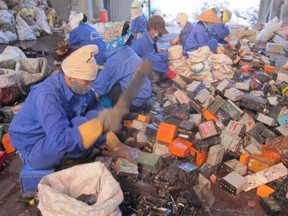 Workers extracting Pb from used batteries